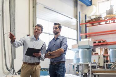 Two men with folder talking in factory storeroom - DIGF03461