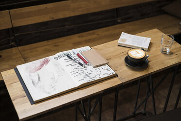 Table in a cafe with coffee mug, notebooks, pens and a glass of water - SBOF01364