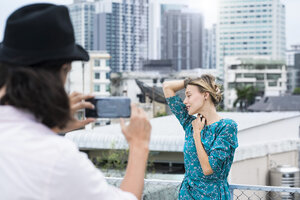 TYoung man with smartphone taking picture of girlfriend posing on rooftop - SBOF01379