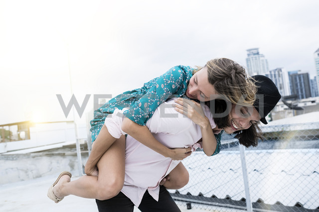Young affectionate couple having fun together on rooftop - SBOF01382