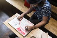 Artist sitting in cafe,  drawing into his notebook - SBOF01385