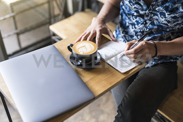 Artist writing into notebook in a cafe with coffee and laptop on the table - SBOF01388