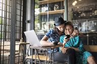 Artist couple sitting in cafe and checking the young woman's smartphone - SBOF01391