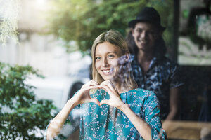 Beautiful young woman making a finger frame heart and smiling at her boyfriend through a window - SBOF01397