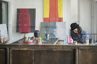 Artist at work, drawing in a notebook in his loft studio - SBOF01400