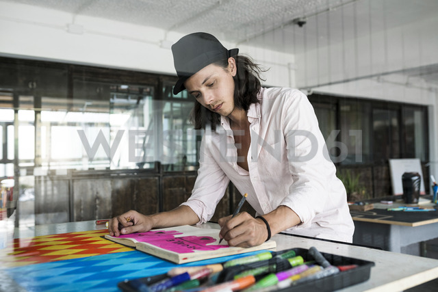 Artist at work, drawing in a notebook in his loft studio - SBOF01406