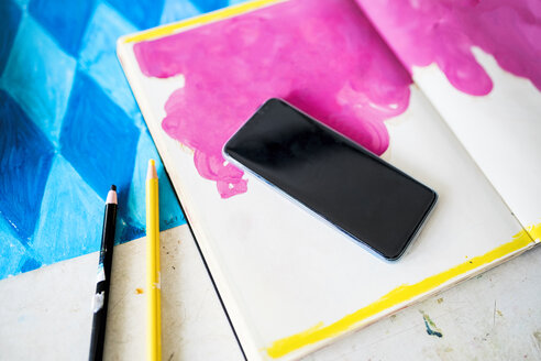 Smartphone lying on a notebook with a pink drawing in artist's studio - SBOF01412