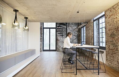 Businessman using laptop in modern office - PDF01445