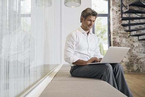 Businessman sitting on bench in modern office using laptop - PDF01448