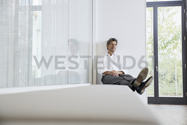 Businessman relaxing on bench in modern office - PDF01457