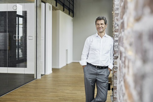 Portrait of smiling businessman leaning against brick wall in modern office - PDF01469