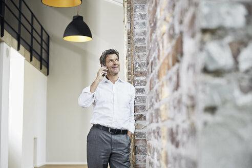Mature businessman using smartphone in modern office - PDF01472
