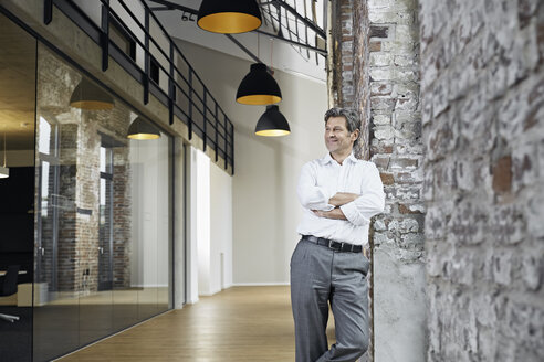 Portrait of smiling businessman leaning against brick wall in modern office - PDF01475