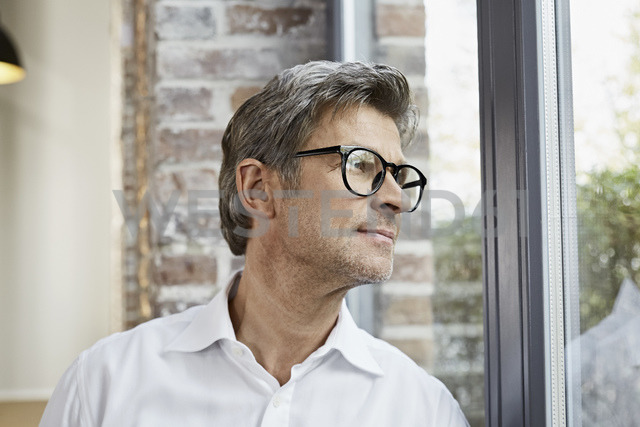 Mature businessman wearing glasses looking out of window - PDF01478