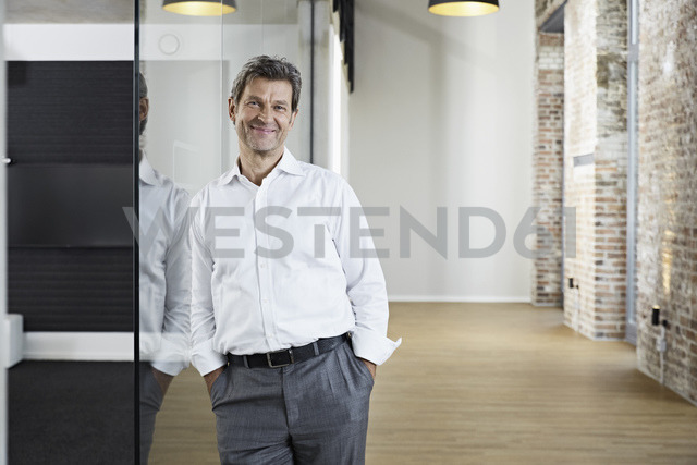Portrait of smiling businessman leaning against glass pane in modern office - PDF01481