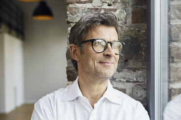 Portrait of smiling businessman wearing glasses looking out of window - PDF01484