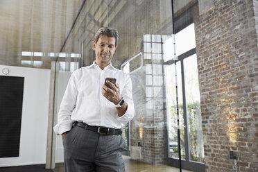 Mature businessman using smartphone in modern office - PDF01487