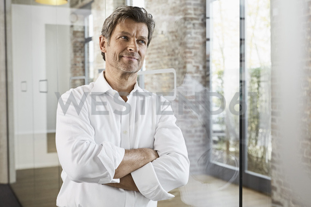 Portrait of mature businessman leaning against glass pane in modern office - PDF01490
