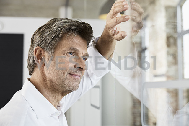 Portrait of mature businessman leaning against glass wall in office - PDF01493
