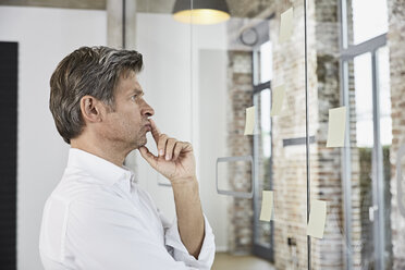 Mature businessman looking at sticky notes at glass pane in office - PDF01496