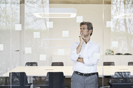 Mature businessman looking at sticky notes at glass  in modern conference room - PDF01499