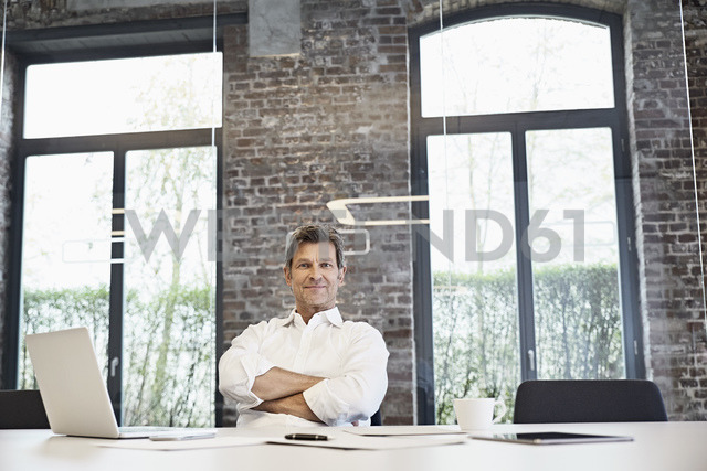 Portrait of mature businessman with laptop in modern office - PDF01502