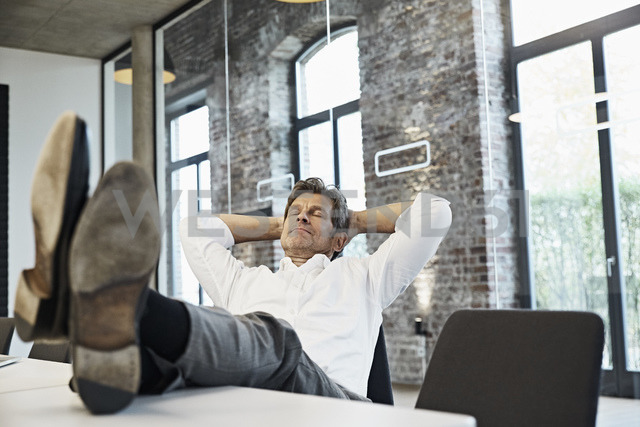 Mature businessman relaxing in conference room of modern office - PDF01505