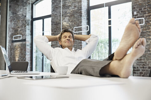 Barefooted businessman relaxing in conference room of modern office - PDF01508