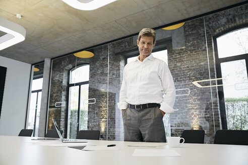 Businessman looking at documents on desk in modern office - PDF01511