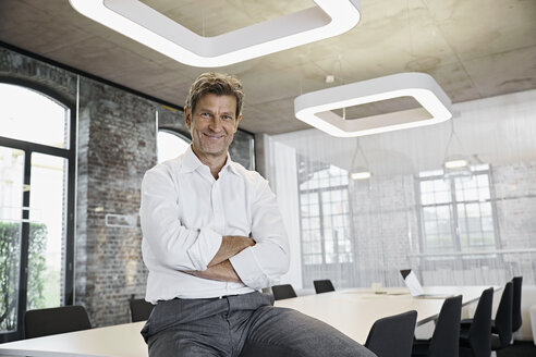 Portrait of confident mature businessman in conference room of modern office - PDF01517