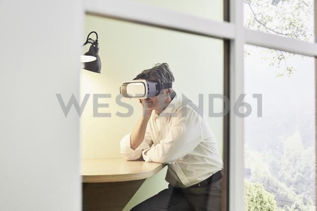 Businessman wearing VR glasses in modern office - PDF01538