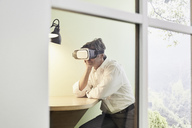 Businessman wearing VR glasses in modern office - PDF01538