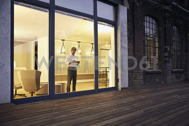 Exterior view of man using tablet in modern building at night - PDF01550