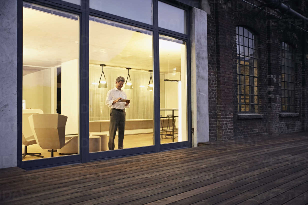 Exterior view of man using tablet in modern building at night - PDF01550 - Philipp Dimitri/Westend61