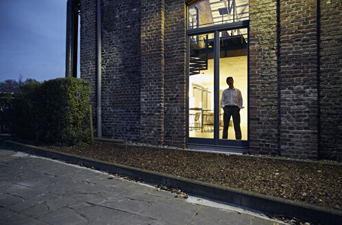 Exterior view of man standing at window of modern building at night - PDF01553