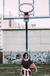 Young woman standing with basketball on outdoor court - VPIF00326