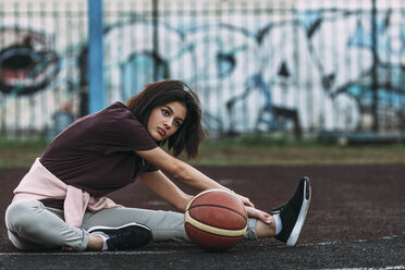 Young woman with basketball stretching on outdoor court - VPIF00329