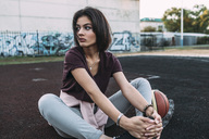 Young woman sitting with basketball on outdoor court - VPIF00332