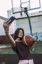 Young woman with basketball taking a selfie on outdoor court - VPIF00335