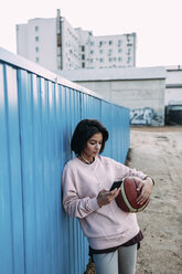 Young woman with basketball, smartphone and earphones at container - VPIF00338