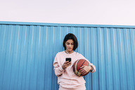 Young woman with basketball, smartphone and earphones at container - VPIF00341