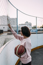 Young woman standing with basketball at fence - VPIF00344