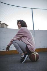 Young woman sitting on basketball outdoors - VPIF00347