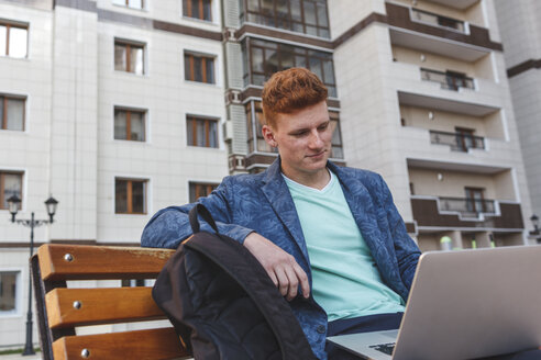 Redheaded young man sitting on bench using laptop - VPIF00350