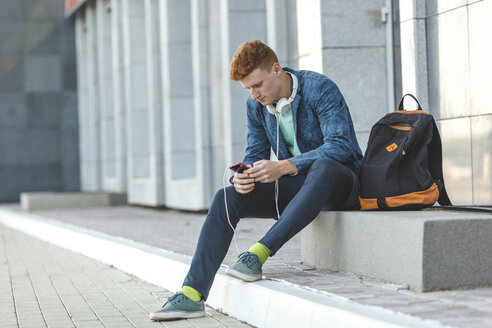 Redheaded young man sitting outdoors with smartphone and headphones - VPIF00353