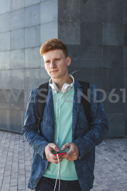 Redheaded young man outdoors with smartphone and headphones - VPIF00356