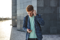 Redheaded young man outdoors with smartphone and headphones - VPIF00359