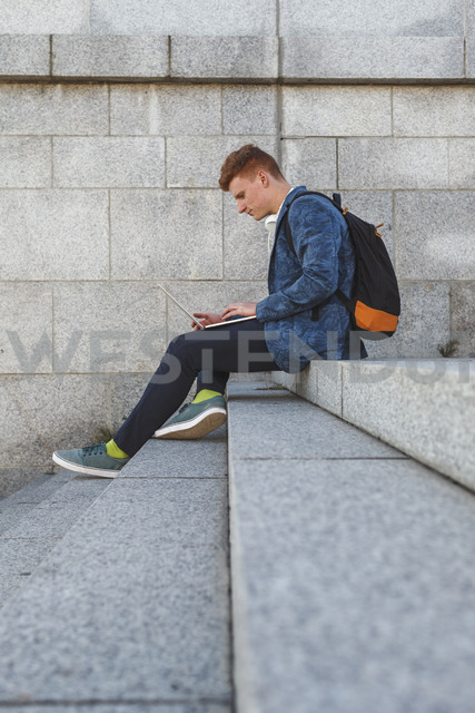 Redheaded young man sitting on stairs using laptop - VPIF00365