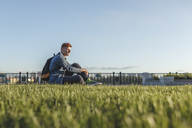 Young man sitting on a meadow - VPIF00371