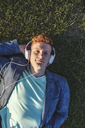 Portrait of redheaded young man with headphones lying on grass - VPIF00374